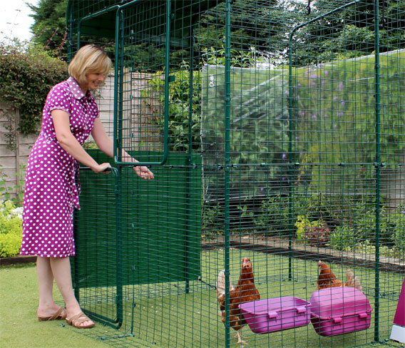 Women opening top half of stable door to the Omlet walk in chicken run.